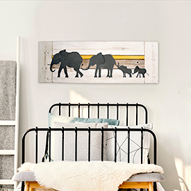 Wooden bench with white fur in front of bed between nightstand with lamp and ladder in bright bedroom with sheep poster